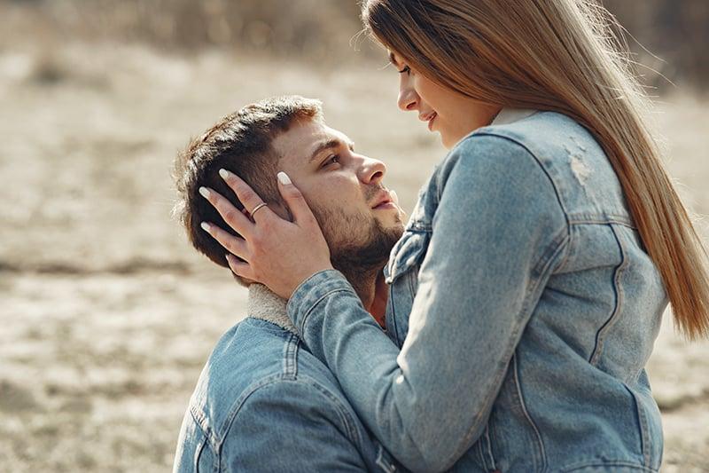 ein liebevolles Paar, das sich auf dem Feld umarmt
