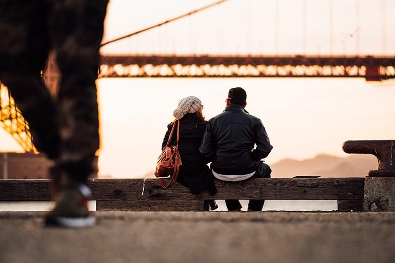 Ein liebevolles Paar sitzt draußen auf der Holzbank und beobachtet den Sonnenuntergang in der Nähe der Brücke