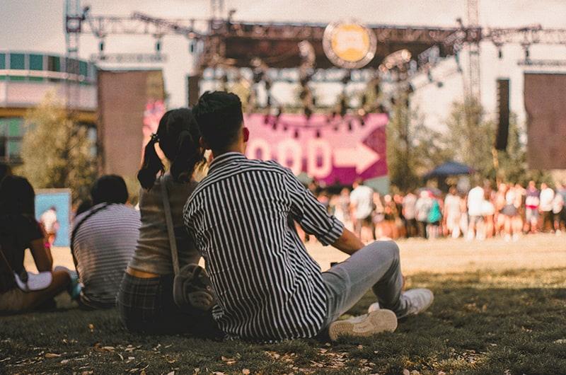 ein liebendes Paar beim Konzert im Gras sitzen