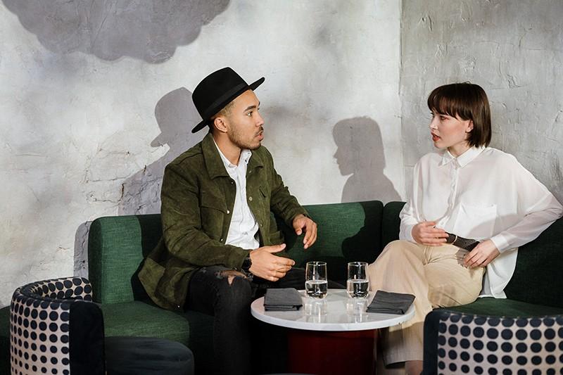 Ein liebevolles Paar bespricht ihre Beziehung und sitzt neben dem Tisch