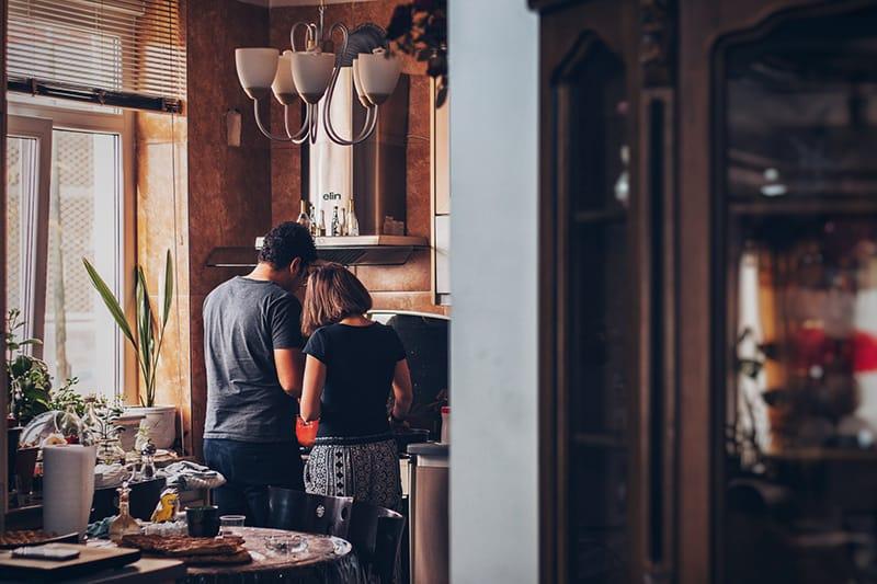 Ein liebevolles Paar, das in einer neuen Wohnung neben dem Herd Essen zubereitet