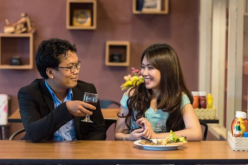 Ein liebevolles Paar, das davon spricht, im Restaurant zusammenzuziehen
