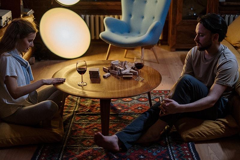 Ein liebevolles Paar, das den Abend zusammen mit einem Spiel aus Holzsteinen verbringt