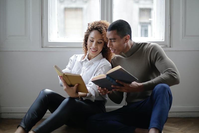 ein liebevolles Paar, das Buch liest, während es zusammen auf dem Boden sitzt