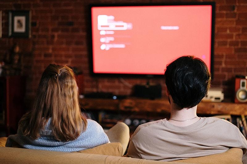 Ein Paar, das abends fernsieht, während es auf der Couch sitzt