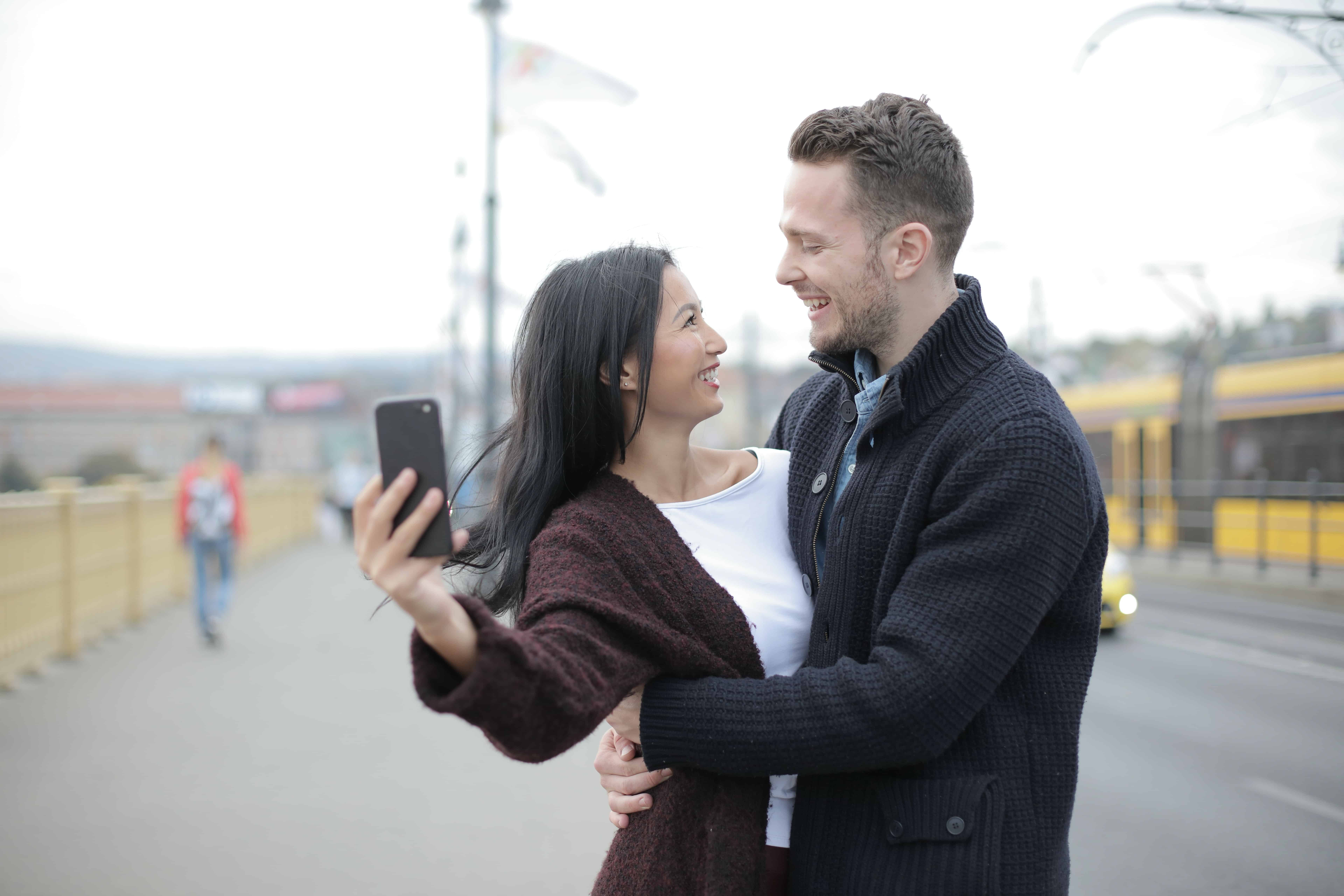 Ein positives Paar macht ein Selfie, während es auf dem Bürgersteig steht