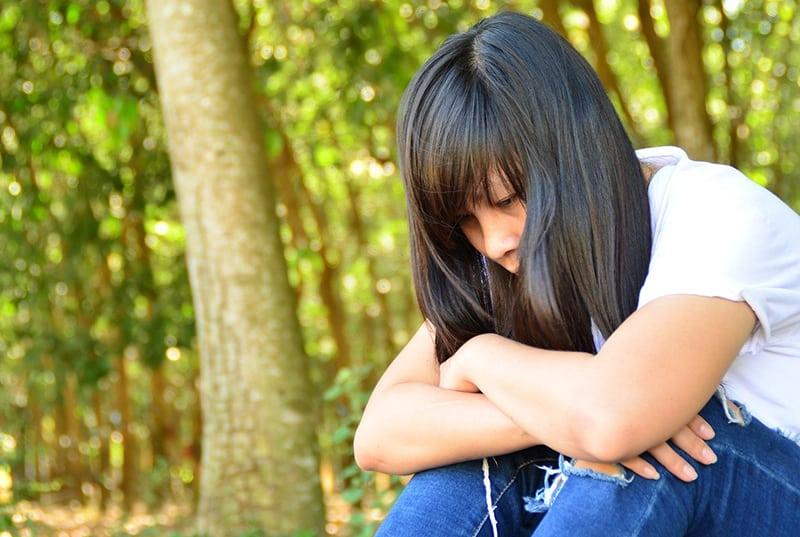 ein trauriges Mädchen, das denkt, während es auf dem Boden im Wald sitzt