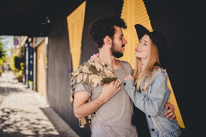 ein umarmendes Paar, das auf dem Bürgersteig steht, während es lächelt