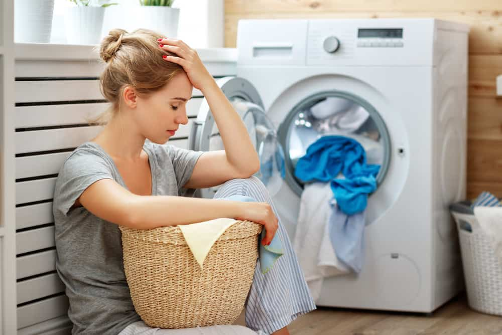 eine Frau überwältigt mit Wäsche auf dem Boden sitzen