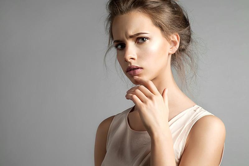 eine Frau denkt nach, während sie ihr Kinn berührt mit Hand