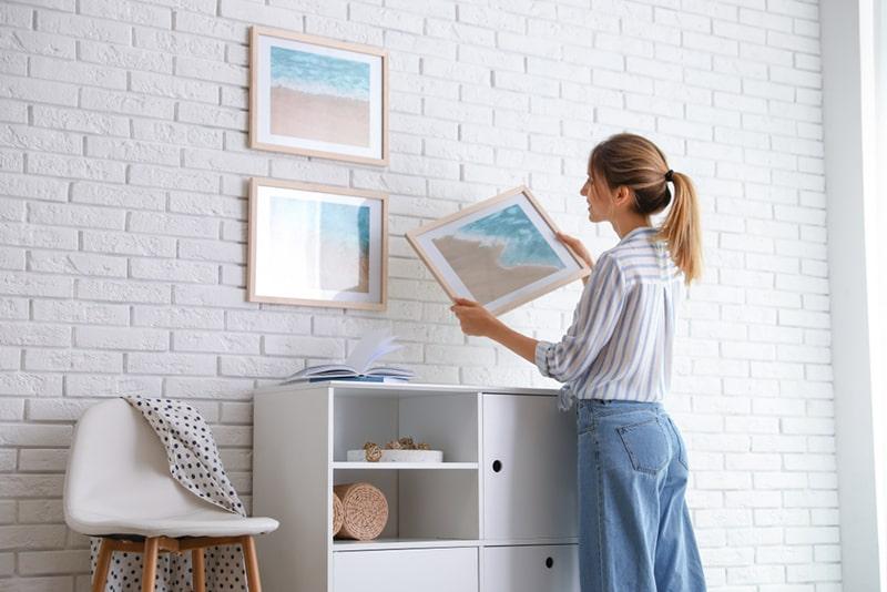 eine Frau, die Bild an einer weißen Backsteinmauer beim Dekorieren des Hauses hängt