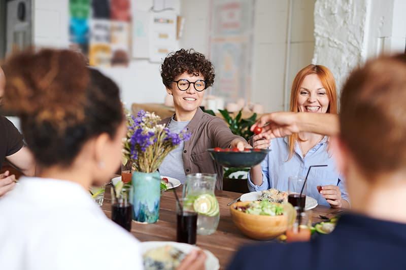 eine Frau, die mittags mit der Familie Essen teilt
