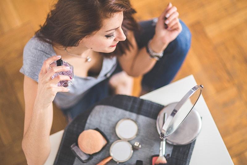 eine Frau, die Parfüm aufträgt, sitzt auf dem Boden