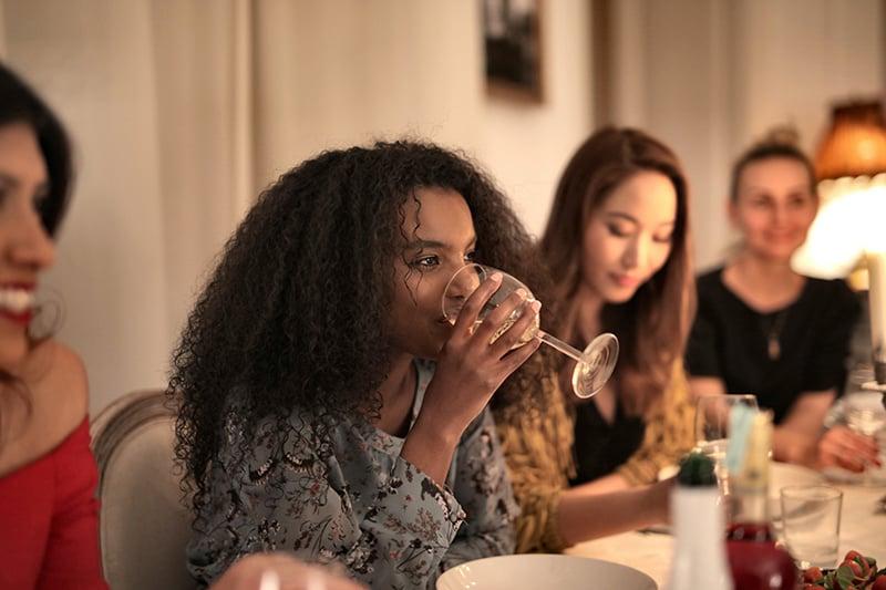 eine Frau, die mit Freunden Wein in einem Diner trinkt