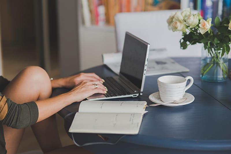 eine Frau, die Zeitplan auf einem Laptop tippt, während sie auf Stuhl sitzt