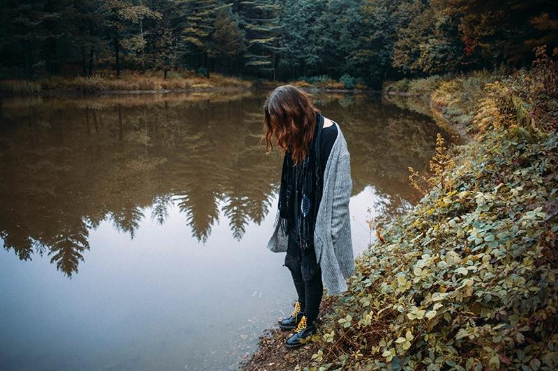 eine Frau, die allein in der Nähe des Flusses steht und hineinschaut