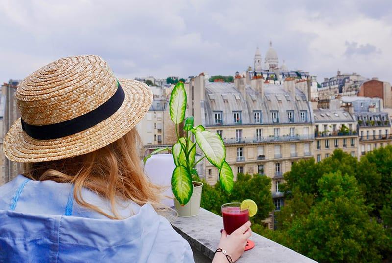 eine Frau, die alleine auf dem Balkon mit einem Drink in der Hand genießt