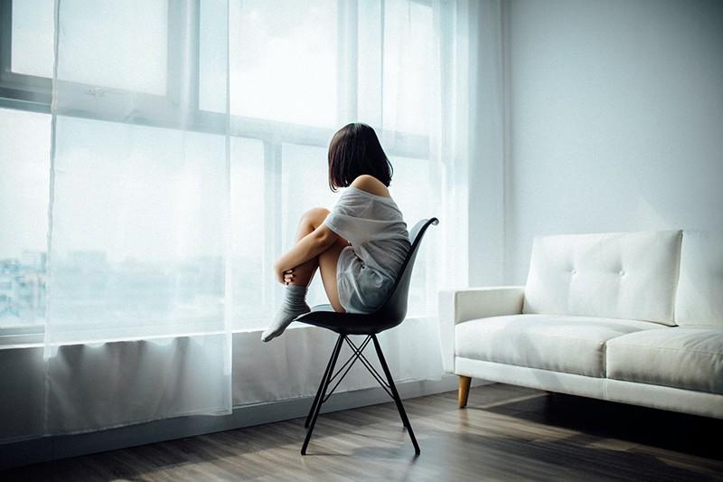 eine Frau, die alleine neben dem Fenster auf dem Stuhl sitzt