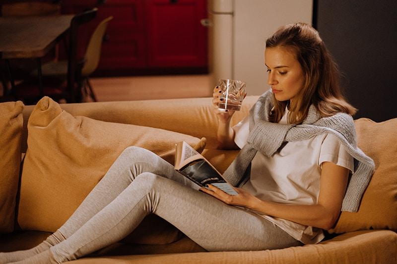 eine Frau, die alleine ruht, während sie ein Buch liest