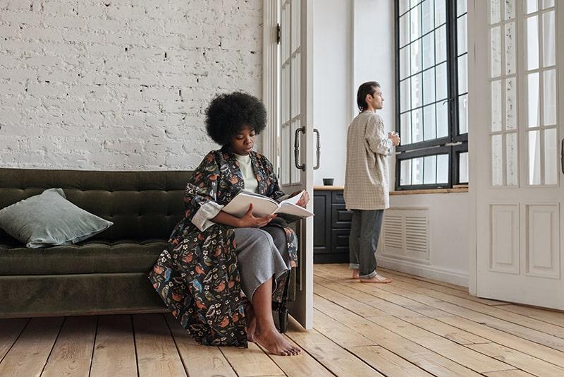 Eine Frau sitzt auf der Couch und liest eine Zeitschrift, während ein Mann am Fenster steht