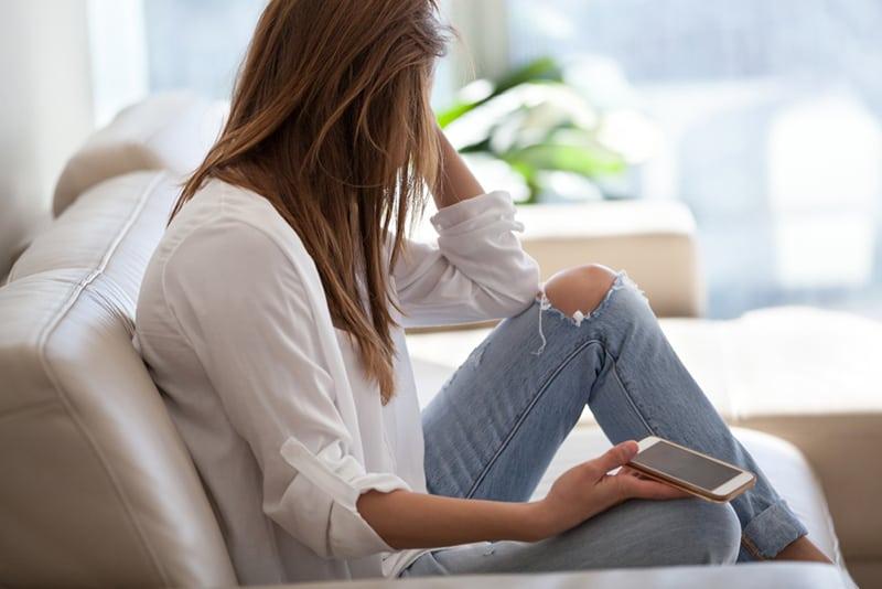 eine Frau, die auf einen Anruf wartet, der auf dem Sofa sitzt