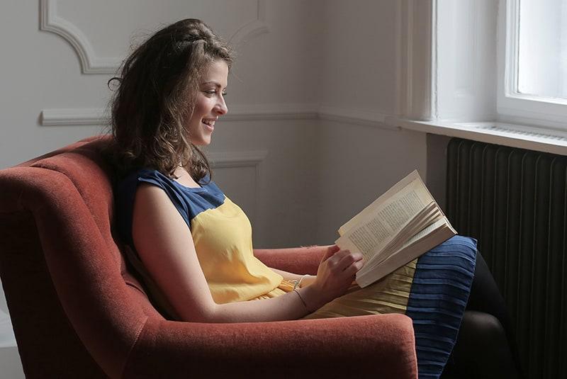 eine Frau, die ein Buch liest, während sie in der Nähe des Fensters sitzt
