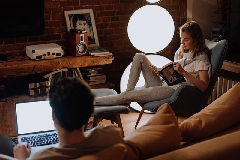 eine Frau, die ein Buch liest, während ein Mann einen Laptop im Wohnzimmer benutzt