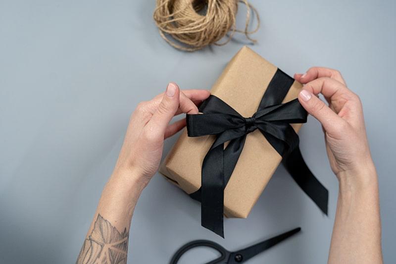 eine Frau, die ein von ihr selbst gemachtes Geschenk einpackt