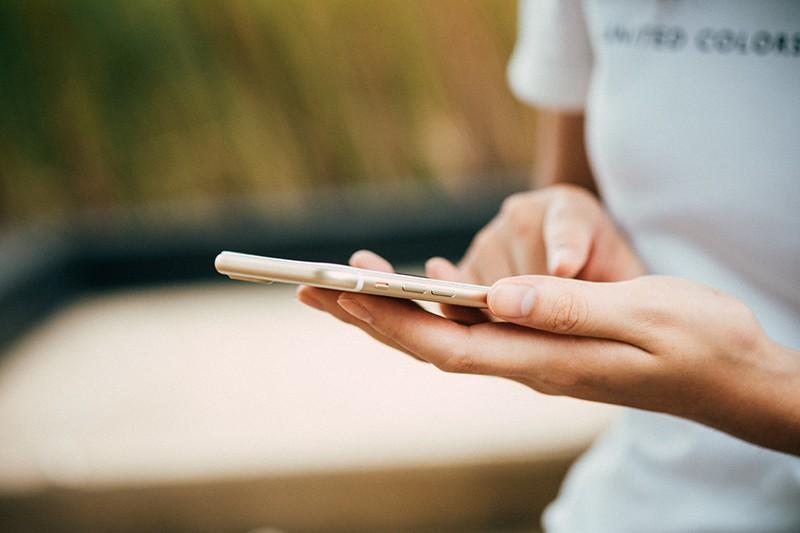 eine Frau, die ein Smartphone in der Hand hält, während sie einen Kontakt löscht