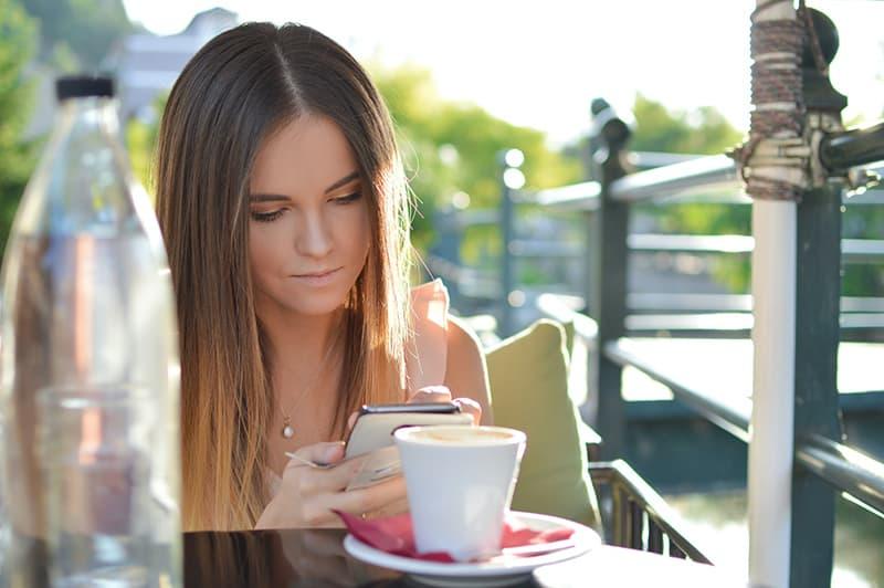 eine Frau, die eine Nachricht auf Smartphone schreibt, während sie in einer Cafeteria sitzt