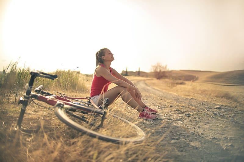 Eine Frau macht eine Pause vom Fahrradfahren und sitzt alleine in der Nähe der Straße