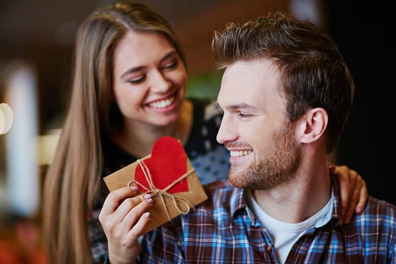 eine Frau, die einem Mann ein kleines Geschenk zum Jubiläum gibt
