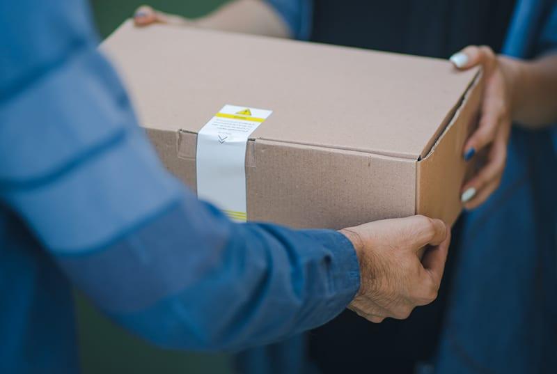 eine Frau, die einem Mann, der ein blaues Hemd trägt, eine braune Schachtel gibt