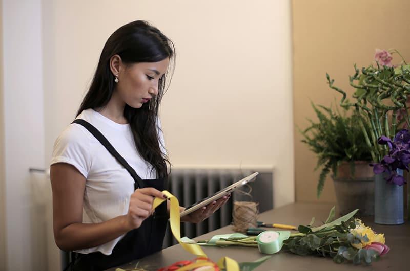 eine Frau, die einen Blumenstrauß macht, während sie eine Tafel im Blumenladen betrachtet