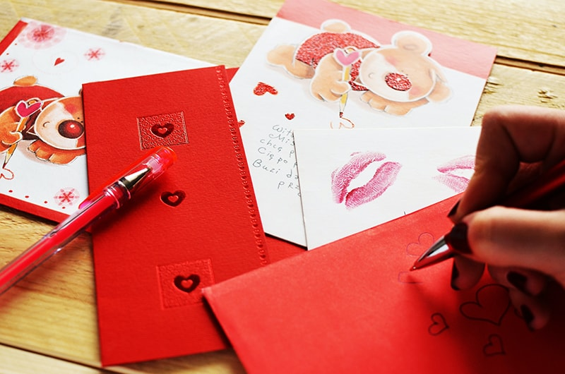 eine Frau, die einen Liebesbrief für ein Geschenk schreibt