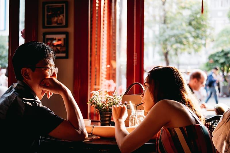eine Frau, die einen Mann mit einem Problem unterstützt, während sie in der Bar sitzt