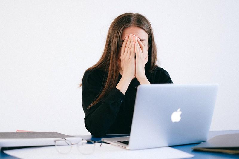 Eine Frau, die ihr Gesicht während eines Videoanrufs mit ihrem Freund mit Handflächen bedeckt, während sie über das Problem spricht