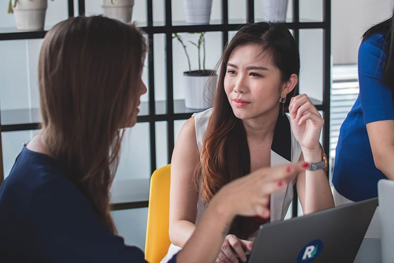 eine Frau, die ihrer Kollegin im Büro zuhört