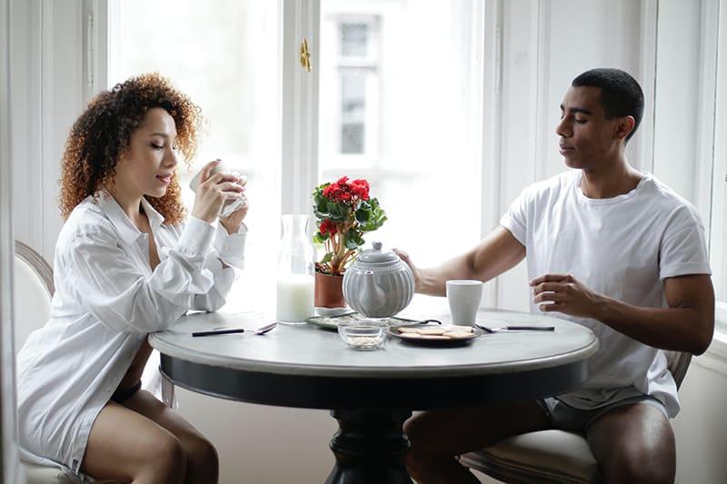 eine Frau, die in Kaffee starrt, während sie neben einem Mann sitzt während des Frühstücks