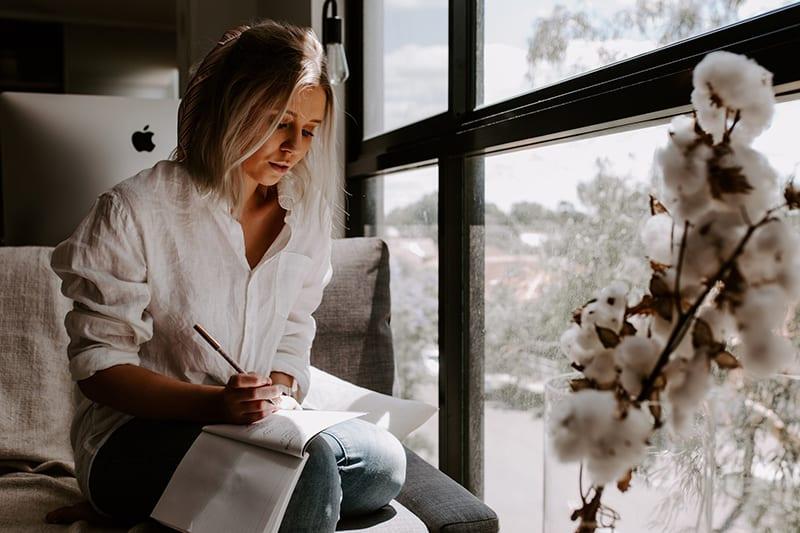 eine Frau, die in das Notizbuch schreibt, während sie neben dem Fenster sitzt