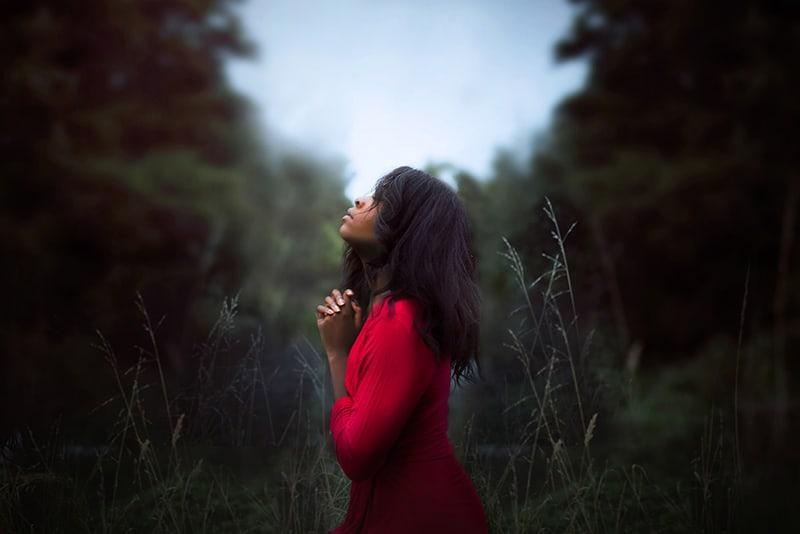eine Frau, die beim Beten in den Himmel schaut