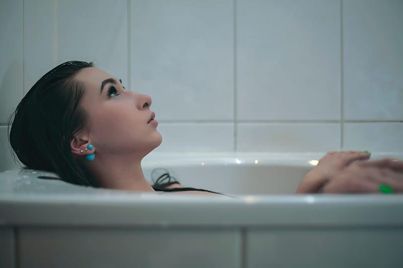 eine Frau, die mit Gedanken kämpft, während sie in der Badewanne liegt
