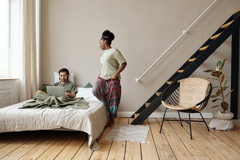 eine Frau, die mit einem Laptop neben dem Mann auf dem Bett sitzen will