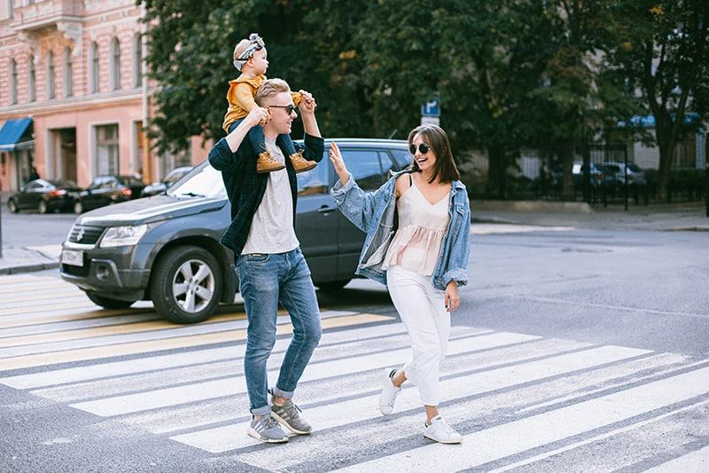 eine Frau, die neben einem Mann mit einem Kind am Hals auf dem Zebrastreifen geht