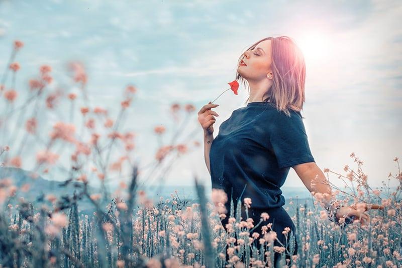 eine Frau, die sich frei fühlt, eine rote Blume im Blumenfeld haltend