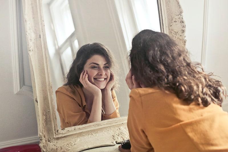 eine Frau, die sich lächelnd in den Spiegel schaut