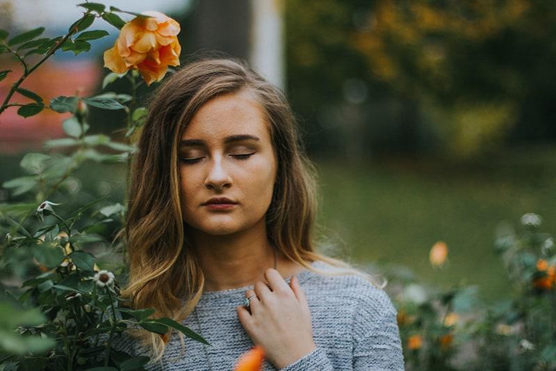 eine Frau, die sich mit ihren Gedanken befasst, während sie mit geschlossenen Augen in der Nähe von Rosen steht