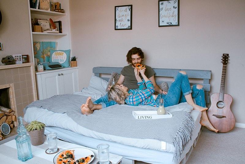 eine Frau füttert einen Mann mit Pizza, während sie auf dem Bett sitzt