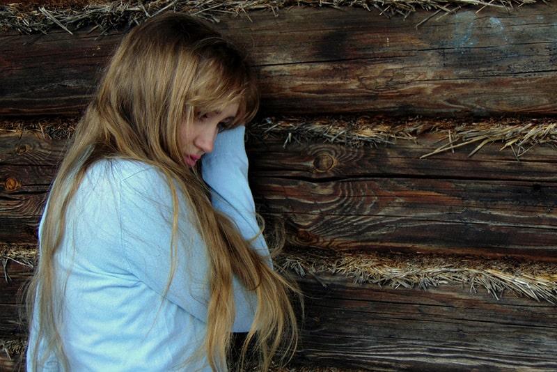 eine Frau im Gefühlschaos mit langen blonden Haaren an die Holzwand gelehnt