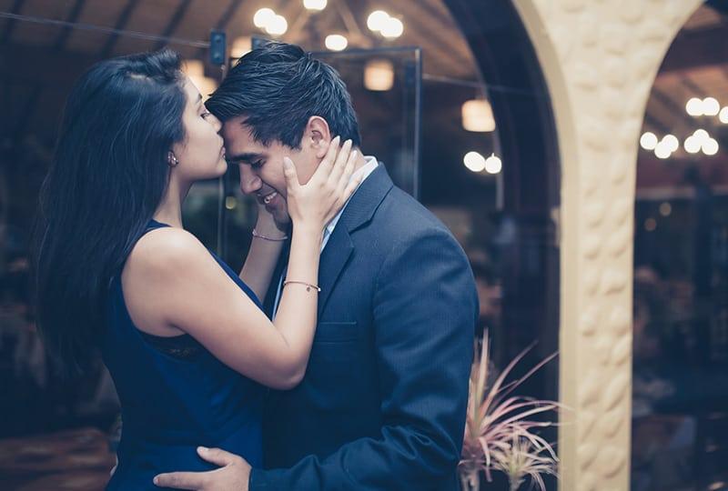 eine Frau, die die Stirn eines Mannes küsst, während sie draußen steht
